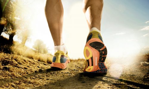 close up feet with running shoes and strong athletic legs of sport man jogging in fitness training workout on off road trail track design in advertising poster style in sunset country background