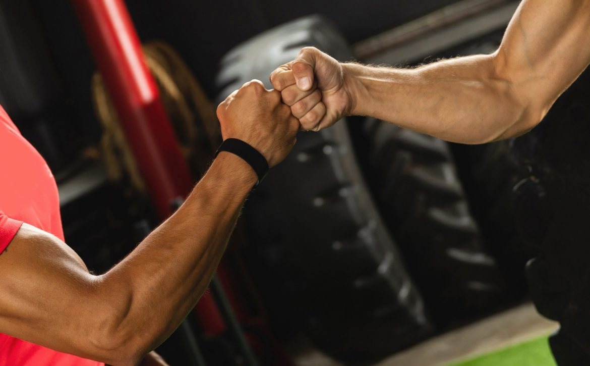 Two muscular men are making fist bump gesture during workout in the gym